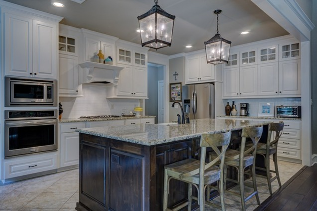 white traditional kitchen, lantern island light fixtures, brown cabinet islands, interior designers in MA